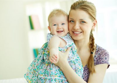 Portrait of happy young mother holding her little daughter