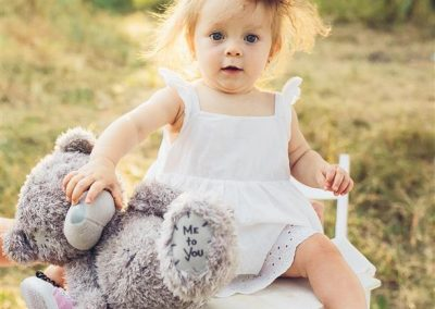 little girl playing with a teddy bear in the garden